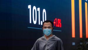 Un hombre camina frente a las pantallas de la bolsa de Shanghai, China