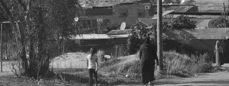 Una mujer y su hija volviendo del centro de Cruz Roja en la Cañada Real