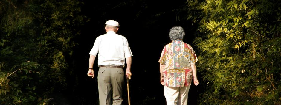 Una pareja de pensionistas caminan por las cercanías de su municipio