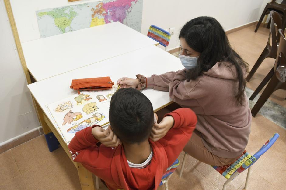 Una voluntaria del Proyecto Alba ayudando a una niña con las tareas del colegio