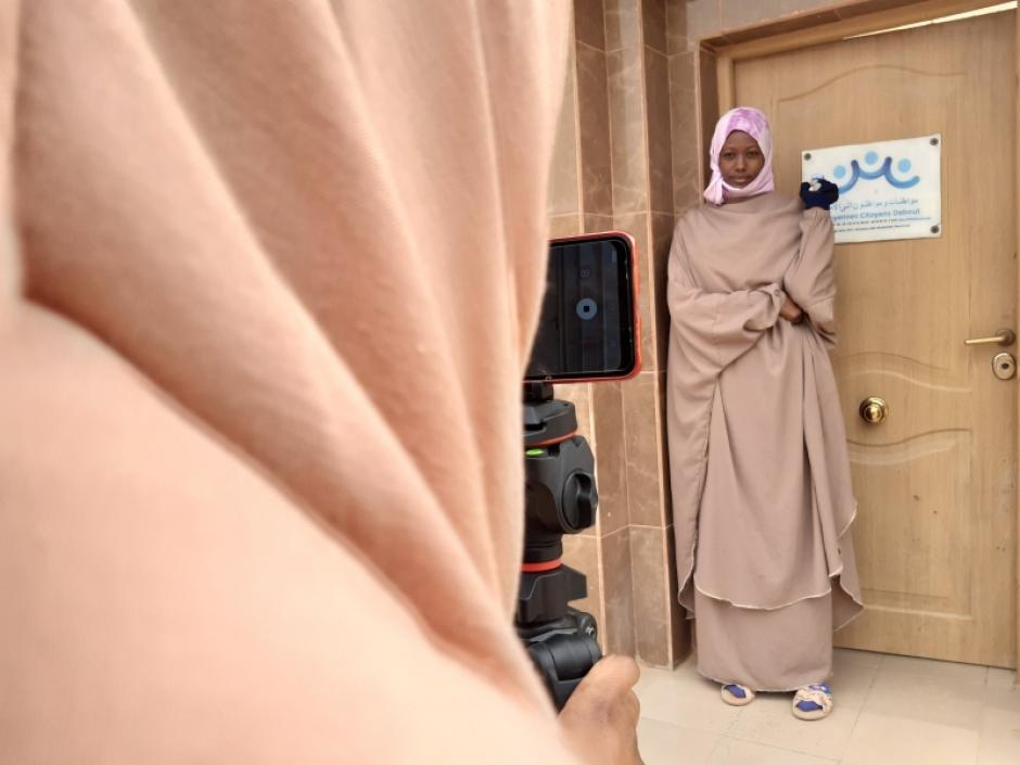 Una joven cuenta frente al centro del socio local de Manos Unidas su testimonio para las redes sociales